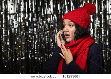 Surprised woman in warm winter clothing talking on cell phone