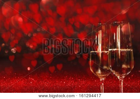 Valentines day background with a sky full of red heart and two glass of champagne for a concept