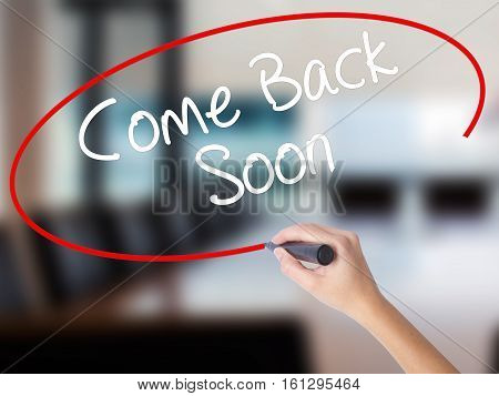 Woman Hand Writing Come Back Soon With A Marker Over Transparent Board.