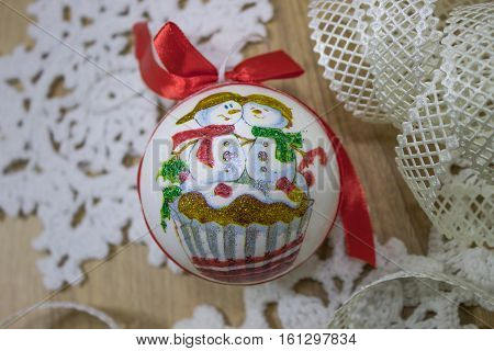 Christmas toy balloon with a ribbon. Handmade decoupage depicted on the ball snowmen