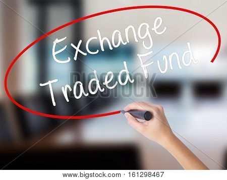 Woman Hand Writing Exchange Traded Fund With A Marker Over Transparent Board.