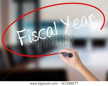 Woman Hand Writing Fiscal Year With A Marker Over Transparent Board.