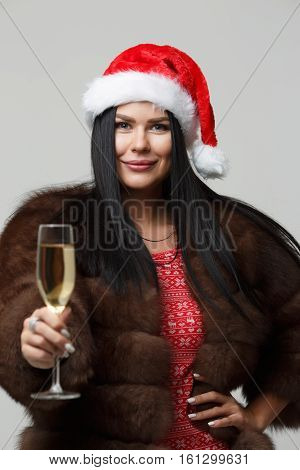 Brunette in mink fur coat isolated on gray background with glass of champagne in hand