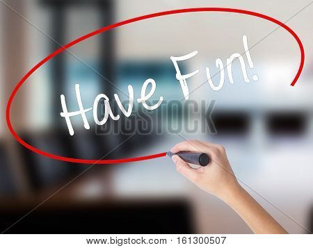 Woman Hand Writing Have Fun! With A Marker Over Transparent Board