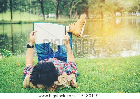 Young man reading a book lying in relaxing bed at park