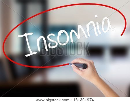 Woman Hand Writing Insomnia With A Marker Over Transparent Board.