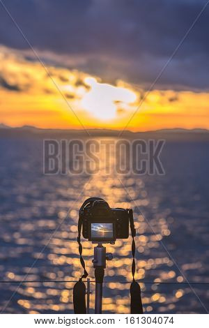 Camera on a tripod capturing the sunset - Colorful image with a DSLR camera on a tripod capturing in live view mode a beautiful sunset over the water.