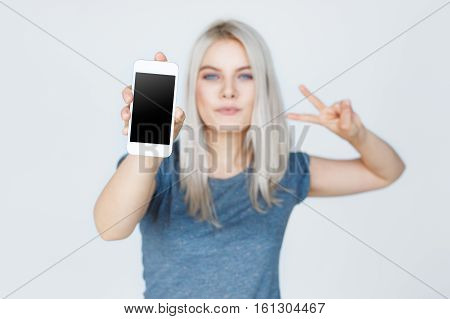 Shallow DOF. Focus on mobile phone. Young woman showing blank smartphone screen and two fingers gesture isolated on grey background.