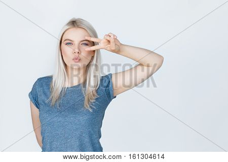 Studio shot of pretty teenage girl with blond hair pouting gesturing peace isolated over gray background