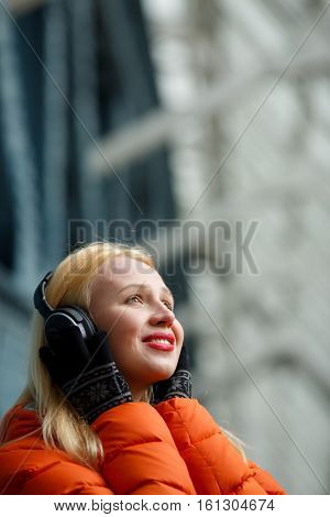 Ginger with headphones listening music in building