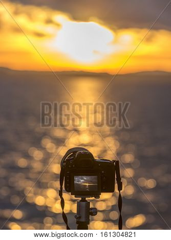Modern DSLR camera on a tripod  - Cropped image with a modern DSLR camera standing on a tripod taking a photo with the sunset over the water in live view mode.