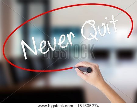 Woman Hand Writing Never Quit With A Marker Over Transparent Board.