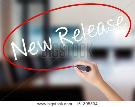 Woman Hand Writing New Release With A Marker Over Transparent Board