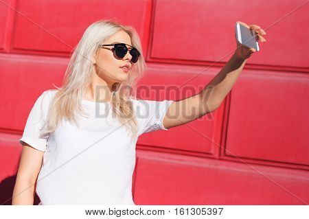 Young blond female blogger with recording video with smartphone, making vlog. Vlogger vlogging outdoors over red wall