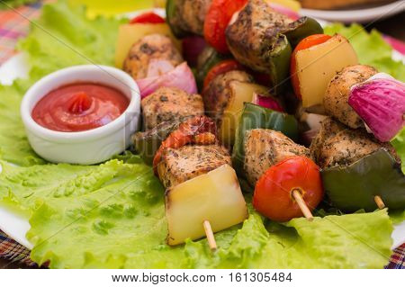 Skewers of chicken and vegetables on wooden skewers. Rural background