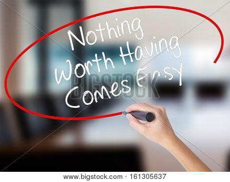 Woman Hand Writing Nothing Worth Having Comes Easy With A Marker Over Transparent Board