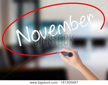 Woman Hand Writing November With A Marker Over Transparent Board