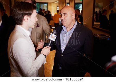 MOSCOW, RUSSIA - JUN 06, 2016: Producer Iosif Prigozhin gives an interview to a journalist at the ceremony of awarding Fashion People Awards in hotel DoubleTree by Hilton - Marina.