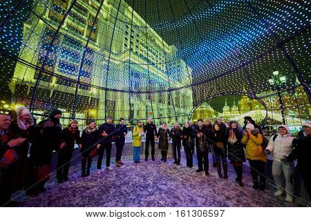 MOSCOW, RUSSIA - JAN 13, 2016: People inside big fishnet Christmas ball at Manege Square during New Year holidays in the evening. Manege Square situated near the Kremlin and the Alexander Garden.