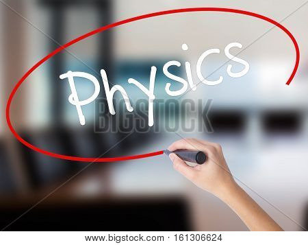 Woman Hand Writing Physics With A Marker Over Transparent Board