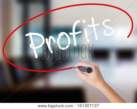 Woman Hand Writing Profits With A Marker Over Transparent Board.