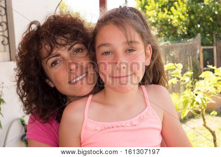 Forties Mother With Ten Years Old Girl In Garden During Summer