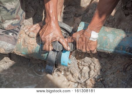 worker male repair plumbing broken pipe in the hole with water flow