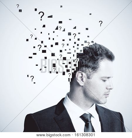 Portrait of businessman puzzled with questions on light background