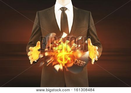 Debt concept. Businessman holding exploding wrecking ball with golden dollar sign inside on dark background