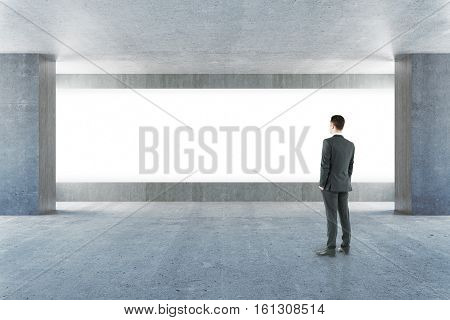 Businessman standing in empty concrete interior with blank billboard. Mock up 3D Rendering