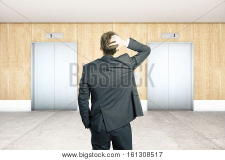 Stressed businessman in interior with two silver elevators wooden wall concrete floor and ceiling. Choice concept. 3D Rendering