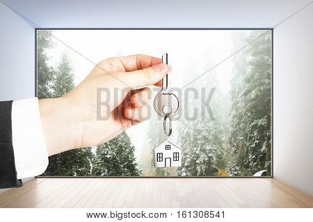 Close up of hand with key in modern interior with panoramic landscape view. Real estate concept