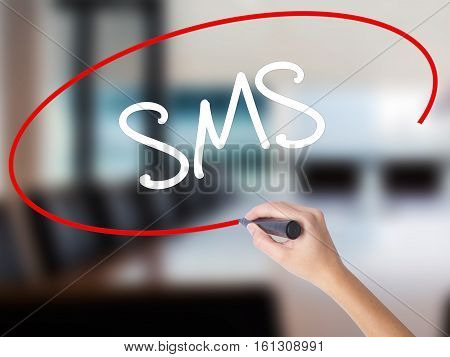 Woman Hand Writing  Sms (short Message Service)  With A Marker Over Transparent Board