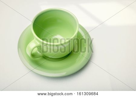 Green teacup on a table with shadow