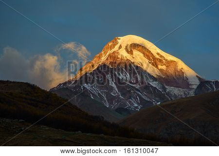 Sunlighted top of snow covered mount against blue sky background. Sunrise scene. Mount Kazbek is one of the major mountains of the Caucasus located in Georgia.