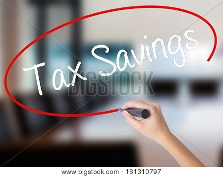 Woman Hand Writing Tax Savings With A Marker Over Transparent Board