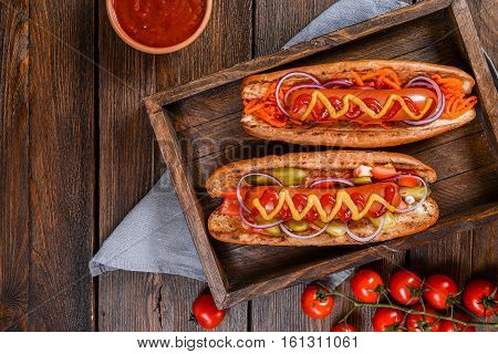 Grilled hot dogs with mustard ketchup and relish on a picnic table