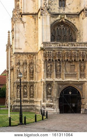 Entrance door and beautiful sculptures on the exterior of Canterbury Cathedral into the summer sunset. Canterbury Kent UK. It is one of the most famous cathedrals in England.