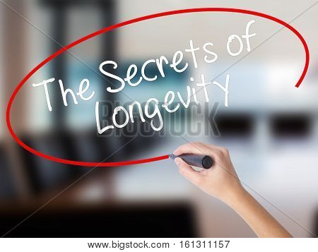 Woman Hand Writing The Secrets Of Longevity With A Marker Over Transparent Board
