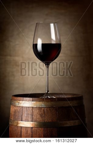 Red wine and barrel on a background of a canvas
