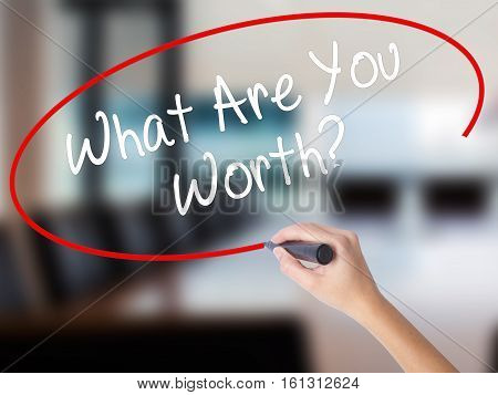 Woman Hand Writing What Are You Worth? With A Marker Over Transparent Board.