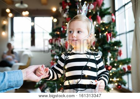 Unrecognizable father with his cute little daughter tangled up in chain of lights at the Christmas tree.