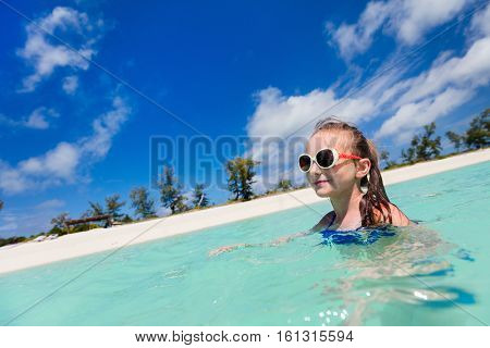 Happy little girl splashing at shallow water at beach having a lot of fun on summer vacation