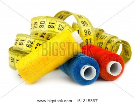 Three colored spools of thread isolated on white background