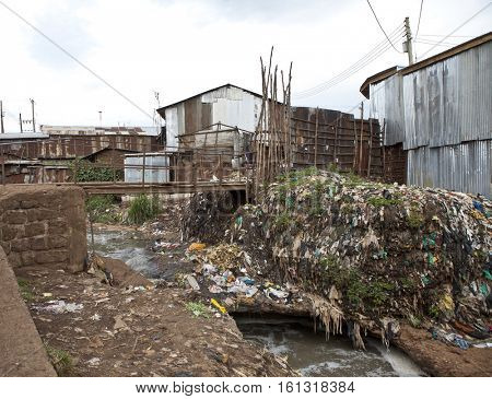 Slum with layers of garbage and filthy water