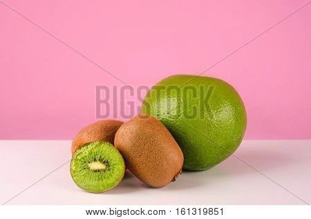 Green pomelo fruit and kiwi on a table isolated on pink background