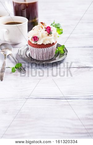 Dessert for Valentines Day, beautiful red velvet cupcake decorated with pink rose on old white wooden background with copy space.