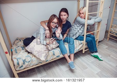 Beautiful girls sitting on a bed in hostel talk and using smartphone.