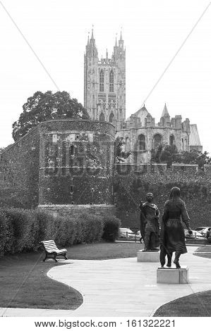 Canterbury Kent United Kingdom - June 16 2006: View of Canterbury Cathedral and City Wall from Lady Wootton's Green where statues of King Ethelbert and Queen Bertha by Stephen Melton into the summer sunset. (black and white)