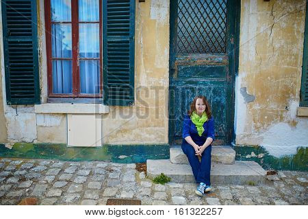 Happy Young Girl Sitting On The Doorstep